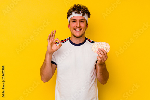 Young sport caucasian man eating a rice cake isolated on yellow background cheerful and confident showing ok gesture Fotobehang