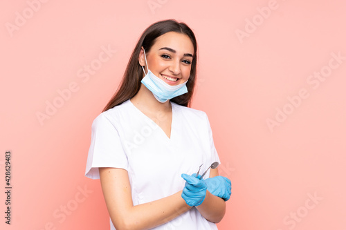 Woman dentist holding tools isolated on pink background laughing - fototapety na wymiar