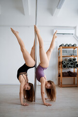 Two sexy women on pole dancing workout