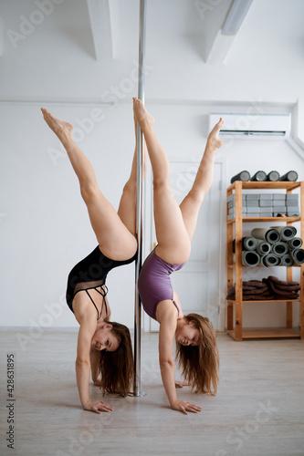 Two sexy women on pole dancing workout - fototapety na wymiar