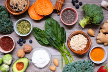 Group Of Healthy Food Ingredients. Overhead View Table Scene On A Wooden Background. Super Food Concept With Green Vegetables, Berries, Whole Grains, Seeds, Spices And Nutritious Items.