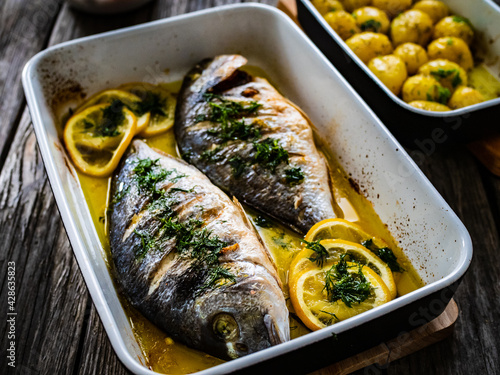 Roast dorada with lemon ,rosemary and potatoes in cooking pan on wooden table