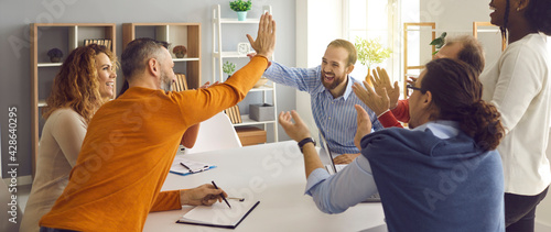 Obraz na plátně Happy successful multiracial business team clapping hands while two colleagues giving high fives gesture each other