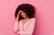 Young african american woman isolated on pink background blink at the camera through fingers, embarrassed covering face.