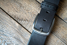 Black Male Leather Belt On A Wooden Background.