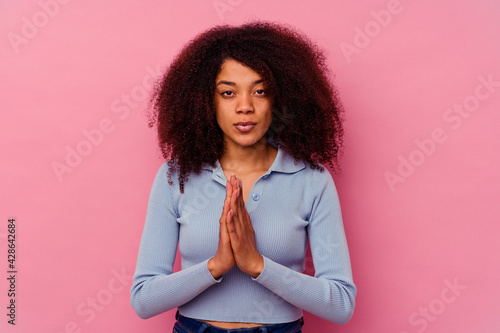 Obraz na plátně Young african american woman isolated on pink background praying, showing devotion, religious person looking for divine inspiration