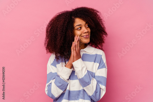 Young african american woman isolated on pink background praying, showing devotion, religious person looking for divine inspiration Fototapet