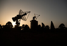 Space Radar Antenna On Sunset. Silhouettes Of Satellite Dishes Or Radio Antennas Against Night Sky. Space Observatory Or Air Defence Radar Over Dramatic Sunset Sky.