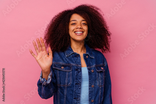 Young african american woman isolated on pink background smiling cheerful showing number five with fingers. - fototapety na wymiar