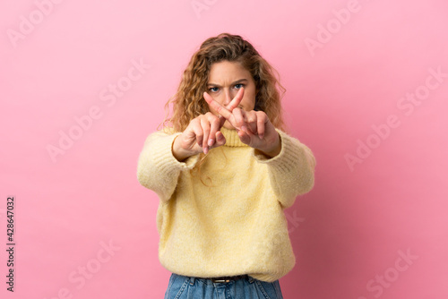 Fototapeta Young blonde woman isolated on pink background making stop gesture with her hand to stop an act obraz