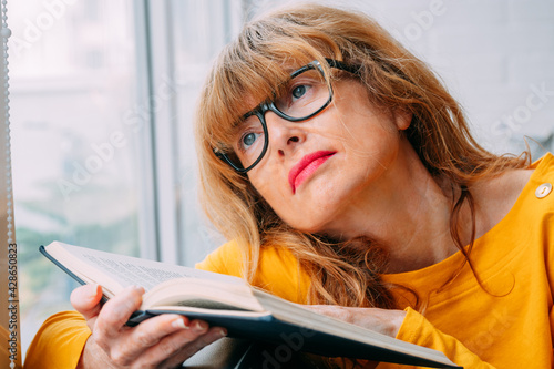 Obraz woman at home with book in the window - fototapety do salonu