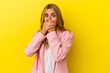Leinwandbild Motiv Young blonde caucasian woman isolated on yellow background covering mouth with hands looking worried.