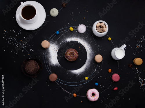 cup of coffee, donuts, macaroons, sugar, milk cream jug and cakes on the  black Poster Mural XXL