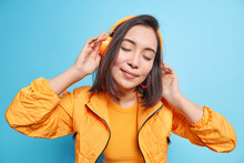 Studio Shot Of Beautiful Brunette Woman Has Eyes Closed Wears Wireless Headphones Listens Music Tilts Head Dressed In Orange Jacket Isolatedover Blue Background. People Lifestyle Hobby Concept