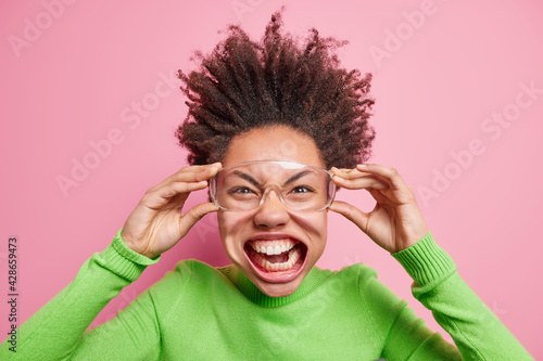 Photo of funny crazy curly girl has opened mouth shows teeth keeps hands on transparent glasses wears green turtleneck being very emotive makes grimace at camera isolated over pink background