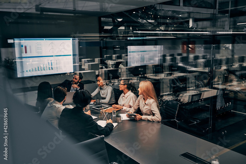 Teamwork. Young focused serious business women and men work in a conference room on a project presentation. Light from a spacious office is reflected through the glass.
