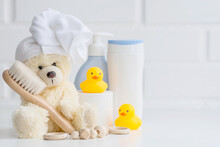 Baby Bath Accessories, Baby Care, A Yellow Bear With A Towel On Its Head, A Brush And Bottles Of Shampoo.