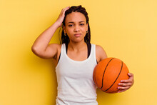 Young African American Woman Playing Basketball Isolated On Yellow Background Being Shocked, She Has Remembered Important Meeting.