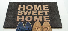 Shoes At Front Door On Entrance Mat Sign Written Home Sweet Home Welcoming Guests At New House Moving In Couple's Pairs Of Sneakers Lying On The Floor.