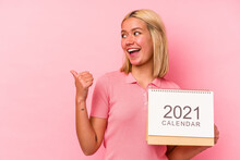 Young Venezuelan Woman Holding A Calendar Isolated On Pink Background Points With Thumb Finger Away, Laughing And Carefree.