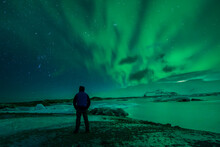 A Man From The Back Watching The Northern Lights. Aurora Borealis.