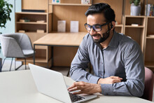 Hispanic Indian Smiling Businessman Wearing Glasses And Headset Having Virtual Team Meeting Call, Talking, Remotely Working At Home Watching Online Learning Training Webinar In Remote Office.