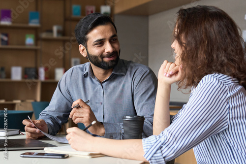 Interview of happy smiling indian hr manager with latin young professional and friendly support discussing job cv. Mentoring Hispanic male teacher and female student in multiethnic creative space.