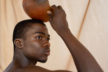 Close-up Of Young African Man Holding Calabash Staring Out Into Distance In Front Of Studio Beige Background
