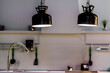 Pair of black hanging lamps above a sink in a modern white kitchen