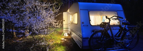 Canvas Print Illuminated caravan trailer and a bicycle on a forest road under a blooming tree in spring at night