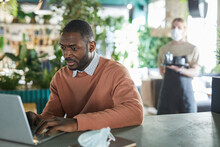 Portrait Of African-American Businessman Using Laptop While Working In Eco Friendly Cafe Interior Decorated With Fresh Green Plants, Copy Space