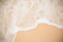 Close Up And Top View Of Glitter Clear Yellow Sand On Beach With Water Wave And White Bubble Shows Beauty Of Natural Vacation Place In Summer Time Under Sunlight. It Shows Clear Sandy Texture Surface.