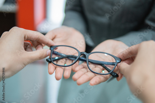 Fotografía a shop assistant's hand gives a pair of glasses to the hand of a customer in an