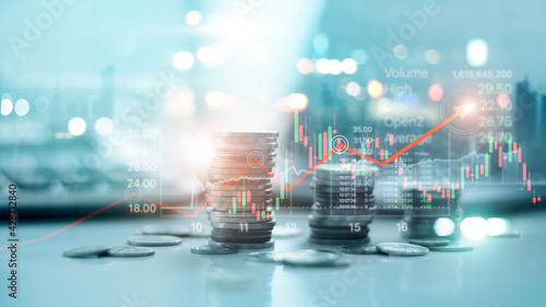 Financial data on a city background. Stack of coins with stock market graph chart background. Idea for banking, financial investment and business growth in world economic development from crisis.