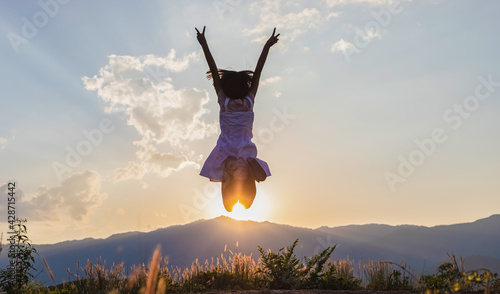 Tela Silhouette of happy child jumping playing on mountain at sunset time