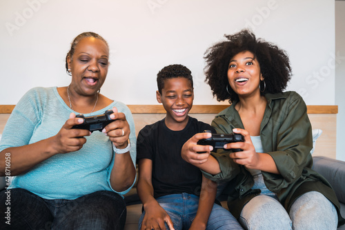 Fototapeta Grandmother, mother and son playing video games at home.