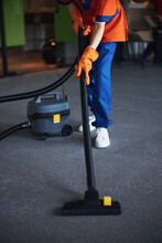 Woman Vacuuming The Floor With A Canister Vacuum Cleaner