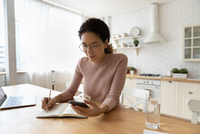 Not To Forget. Busy Young Latin Woman Copy Out Important Information From Phone Memory To Paper Daybook. Female Student Wear Glasses Take Notes Do Paperwork At Home Office In Kitchen Use Cell Copybook