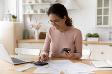 Young Latina Female Work With Financial Papers At Home Count On Calculator Before Paying Taxes Receipts Online By Phone. Millennial Woman Planning Budget Glad To Find Chance For Economy Saving Money