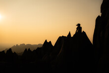 Silhouette Of Young Asian Man Sitting On Beautiful Sharp Shape Limestone Mountains With One Hand Shading His Eyes From The Sun While Admiring Landscape In Front Of Him With Orange Sky In Background.