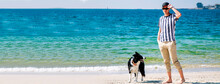 Man Walking With His Dog On The Beach