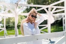 Glamorous Young Lady Enjoy Lifestyle And Posing Against In White Wooden Gazebo Near Lake Beach