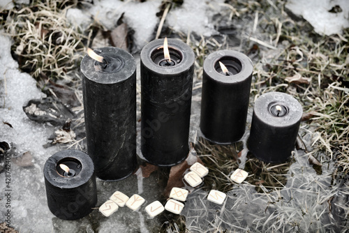 Obraz na plátně Group of burning black candles and runes in the water