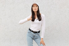 Beautiful Dark Haired Female Wearing Stylish Clothing And Baseball Cap, Looking At Camera, Pouts Lips To Kiss, Touching Her Hair, Expressing Love And Romance, Standing Against Light Wall.