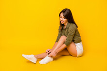 Full Length Profile Portrait Of Gorgeous Lady Sit Hand Tie Shoe Laces Isolated On Yellow Color Background