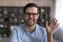 Close Up Profile Screen View Picture Of Smiling Young Caucasian Man In Glasses Wave Greet Talk On Video Call Online. Headshot Portrait Of Happy Male Have Webcam Digital Virtual Event Or Conference.