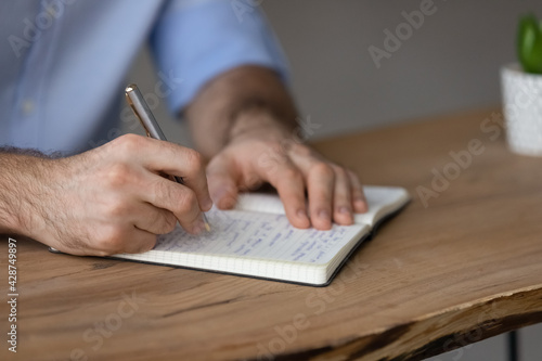 Obraz Crop close up of Caucasian man sit at desk write in notepad, make list or plan. Millennial male handwrite in notebook, involved in time management activity. Distant education, planner concept. - fototapety do salonu