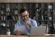 Happy Caucasian Man Sit At Desk Work Online On Computer Read Paperwork Document Get Good News Or Message. Smiling Young Male Consider Paper Contract Or Statistics Busy With Laptop At Workplace.