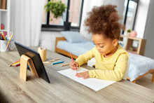 Childhood, Creativity And Art Concept - Little African American Girl With Coloring Pencils Drawing Picture On Paper At Home