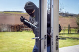 Fototapeta Big Ben - Burglar breaking into a house via a window with a crowbar